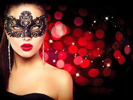 image of face mask  - Sexy model woman in venetian masquerade carnival mask at party over holiday glowing red background - JPG
