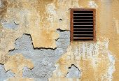 stock photo of grids  - retro wall crumbling plaster coat and rusty ventilation grid - JPG