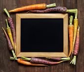 foto of carrot  - Fresh organic rainbow carrots and chalkboard on wood - JPG