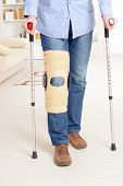 pic of caged  - Man with leg in knee cages and crutches for stabilization and support  - JPG