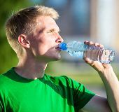 stock photo of plastic bottle  - Tired man drinking water from a plastic bottle after fitness time and exercising in city street park at beautiful summer day - JPG