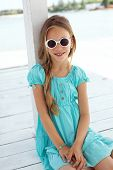 stock photo of preteen  - Preteen child wearing aqua blue fashion clothes resting at the beach in summer - JPG