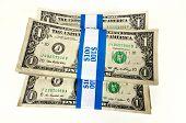 stock photo of bundle  - Three stacks of paper bundled dollars on a white background - JPG