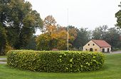 stock photo of farmhouse  - View into a garden park and a few yellow buildings - JPG