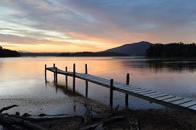 stock photo of jetties  - This old rickety timber plank jetty juts out into Wallaga Lake the largest lake in southern NSW - JPG