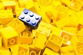 Pile of yellow color building blocks with selective focus and highlight on one particular blue block poster