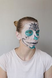 stock photo of day dead skull  - Attractive young blond girl with face painting for the day of the Dead - JPG