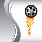 flaming racing tire on vertical silver wave background