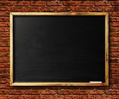 Blank chalkboard in wooden frame on brick wall