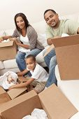 African American family, parents and son, unpacking boxes and moving into a new home, The adults are unpacking crockery and homeware, the child is unpacking a toy airplane.