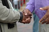 stock photo of condolence  - Two African American men shaking their black hands as a sign of big friendship and to welcome - JPG