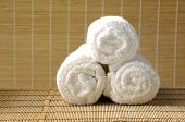 rolled up white spa towel on woven mat background