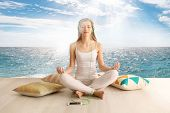 Young woman meditating in lotus pose on seascape background. Concept of music for sleep poster