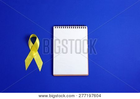 Yellow Ribbon And Notebook On