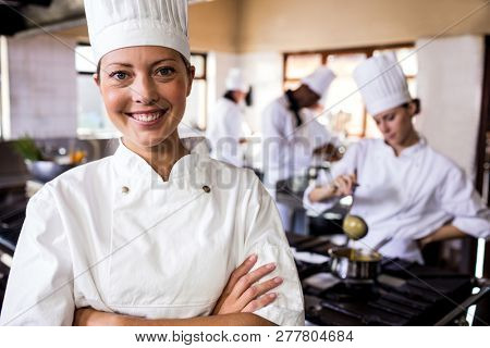 poster of Female chef standing with arms crossed in kitchen at hotel