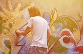Photo In The Process Of Drawing A Graffiti Pattern On An Old Concrete Wall. Young Long-haired Blond  poster