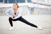 Fitness. Woman Doing Stretching Exercise On Stadium Background poster