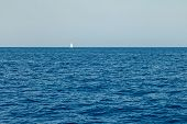 A Lone White Sailing Yacht Sails In The Waters Of The Mediterranean poster