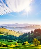Bright rolling countryside around a farm in the morning light. Picturesque day and gorgeous scene. L poster