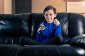 8 Year Old Boy Wearing Sportive Clothing With Asthma Inhaler Sitting In Sofa With Clenched Fist. Con poster