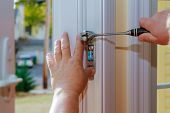 Closeup Of A Professional Locksmith Installing Or Repairing A New Deadbolt Lock On A House Door With poster