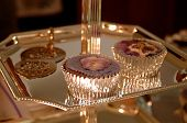 picture of picking tray  - Two cupcakes on a silver tray with a little utensil to pick them up with