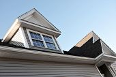 image of gabled dormer window  - Close up view of a newly built house rooftop soffit and dormers - JPG
