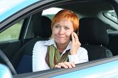 Red-Haired Woman With Mobile-Phone In A Car. She Is Thinking Oups