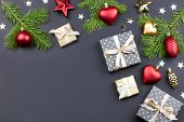 Festive Christmas Background With Fir Branches, Giftboxes, Red Decorations On Black, Copy Space poster