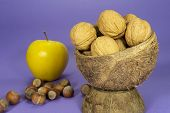Whole Common Walnuts With Shells In Natural Coconut Shell Cup, Pile Of Whole Hazelnuts And Yellow Ap poster