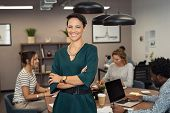 Portrait of sucher colleagues working in background at ofcessful business woman standing with fice.  poster