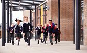 Primary school kids, wearing school uniforms and backpacks, running on a walkway outside their schoo poster