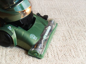 stock photo of house cleaning  - a green vacuum cleaner sweeping the carpet - JPG