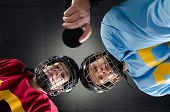 stock photo of hockey arena  - Cloesup of a hockey faceoff with teenage hockey players and puck - JPG