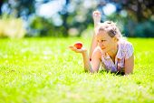 Girl on green grass looking on red apple