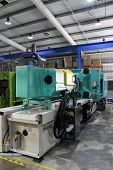 stock photo of thermoplastics  - Injection moulding machine used for the forming of plastic parts using plastic resin and polymers - JPG