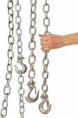 stock photo of perversion  - chain with a hook in the hands of crane operator at construction site - JPG