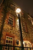 pic of lamp post  - a lamp post by a brick building - JPG
