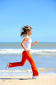 image of workout-women  - young woman jogging on the beach on a warm summer day - JPG