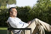 Side view of happy man sitting on chair in backyard