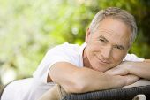 Portrait of middle aged man relaxing on deck chair in garden