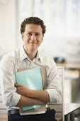 Retrato de joven empresario feliz con archivos de pie por cubículo