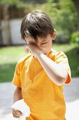 stock photo of influenza  - Young boy with tissue paper rubbing eye in backyard - JPG