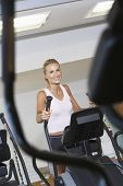 Smiling young woman working out on elliptical machine at gym