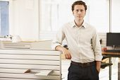 Portrait of confident young businessman standing by cubicle