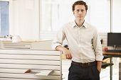 Retrato de confianza empresario joven parado por cubículo