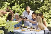 Happy family toasting wine glasses at table in back yard