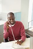 Smiling African American businessman using landline at desk
