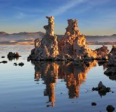 Yosemite National Park, USA. Outliers -  bizarre calcareous tufa formation  reflected in the mirrored surface of the water. The picturesque sunset at Mono Lake