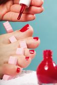 foto of painted toenails  - foot pedicure applying woman - JPG